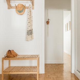 Aménagement d'un hall d'entrée scandinave avec un mur blanc, un sol en bois clair, un sol marron et une porte blanche.