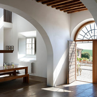 Cette image montre une porte d'entrée minimaliste avec un mur blanc, une porte double, une porte en bois brun et un sol marron.