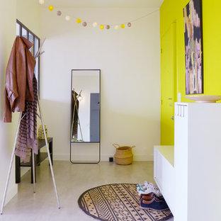 Idées déco pour un grand hall d'entrée contemporain avec un mur jaune, béton au sol, une porte simple, une porte jaune et un sol gris.