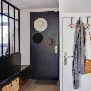 Idée de décoration pour une entrée design de taille moyenne avec un couloir, un mur blanc, une porte simple, une porte noire, un sol marron et un sol en carrelage de céramique.