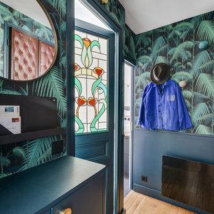 Réalisation d'une entrée design avec un mur multicolore, un sol en bois brun, une porte simple, une porte bleue et un sol beige.