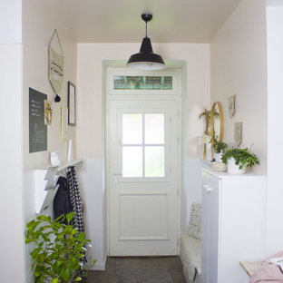 Entryway - small scandinavian dark wood floor entryway idea in Other with pink walls and a white front door