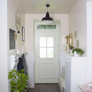 Идея дизайна: маленькое фойе в скандинавском стиле с розовыми стенами, темным паркетным полом, одностворчатой входной дверью и белой входной дверью