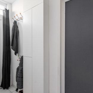 Foto di un ingresso minimalista di medie dimensioni con pareti bianche, pavimento in terracotta, una porta singola, una porta bianca e pavimento bianco