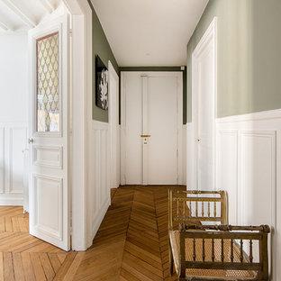 Inspiration pour une entrée traditionnelle avec un couloir, un mur vert, un sol en bois brun, une porte simple, une porte blanche et un sol marron.