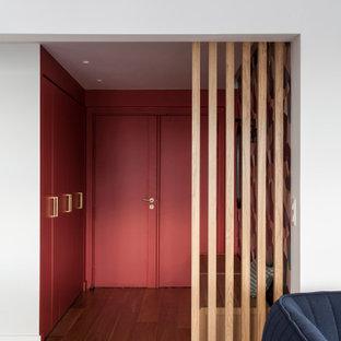 Diseño de distribuidor actual, de tamaño medio, con paredes rojas, suelo de madera clara, puerta doble y puerta roja