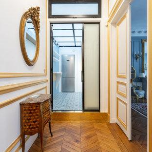 Inspiration för små klassiska foajéer, med vita väggar, mellanmörkt trägolv, en vit dörr och brunt golv