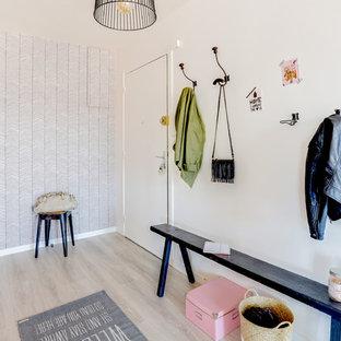 Cette image montre une entrée nordique avec une porte simple, un mur blanc, un sol en bois clair et une porte blanche.