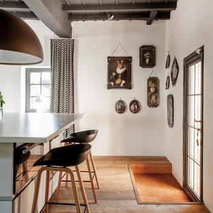 Exemple d'une porte d'entrée nature de taille moyenne avec un mur blanc, un sol en bois brun, une porte simple et une porte noire.