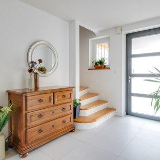 Idée de décoration pour un hall d'entrée design de taille moyenne avec un mur blanc, un sol en carrelage de céramique, une porte simple, une porte grise et un sol beige.