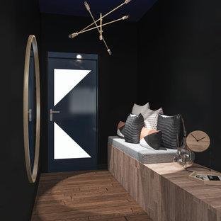 Exempel på en mellanstor industriell hall, med svarta väggar, mörkt trägolv, en enkeldörr och brunt golv