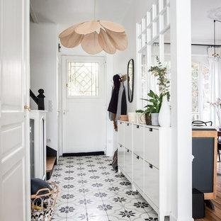 Aménagement d'une petit entrée contemporaine avec un couloir, un mur blanc, une porte simple, une porte blanche et un sol multicolore.