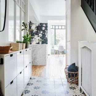 Immagine di un piccolo corridoio contemporaneo con pareti bianche, una porta singola, una porta bianca e pavimento multicolore