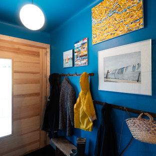Cette image montre une petit porte d'entrée vintage avec un mur bleu, un sol en carrelage de céramique, une porte simple, une porte en bois clair, un sol gris, un plafond en papier peint et du papier peint.