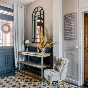 Réalisation d'une porte d'entrée tradition de taille moyenne avec un mur rose, un sol en carrelage de céramique, une porte double, une porte noire et un sol multicolore.