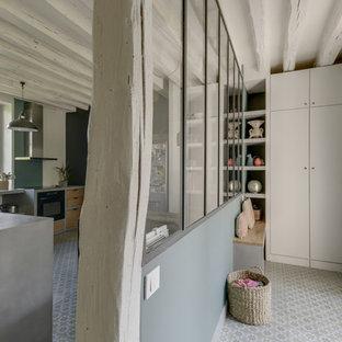 Aménagement d'une entrée industrielle de taille moyenne avec un couloir, un mur vert, un sol en carreau de terre cuite, une porte double, une porte blanche et un sol vert.