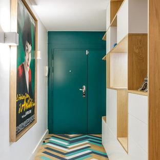 Réalisation d'un hall d'entrée nordique de taille moyenne avec un mur blanc, une porte simple, un sol multicolore, un sol en bois clair et une porte bleue.