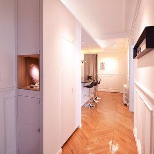 Foto di un corridoio minimal di medie dimensioni con pareti bianche, pavimento in legno massello medio, una porta a pivot, una porta bianca e pavimento marrone