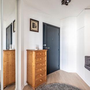 Réalisation d'une entrée tradition avec un mur blanc, un sol en bois clair, une porte simple, une porte noire et un sol beige.