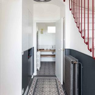 Réalisation d'une entrée design avec un couloir, un mur blanc et un sol multicolore.