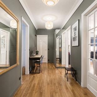 Inspiration för moderna foajéer, med gröna väggar, ljust trägolv, en vit dörr och beiget golv