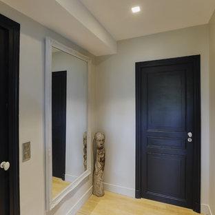 Mittelgroßer Eingang mit Korridor, beiger Wandfarbe, Sperrholzboden, Einzeltür, schwarzer Tür und beigem Boden in Paris