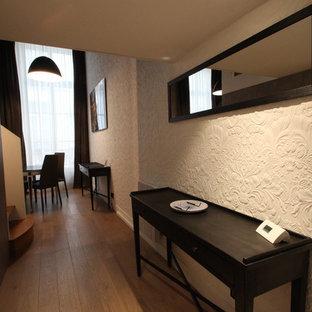 Cette photo montre une entrée tendance de taille moyenne avec un couloir, un mur beige et un sol en bois brun.
