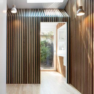 Idées déco pour une entrée contemporaine avec un sol en bois clair et un sol beige.