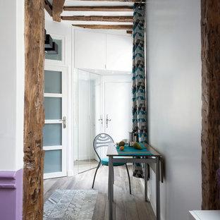 Idées déco pour un hall d'entrée contemporain de taille moyenne avec un mur blanc et un sol en bois brun.