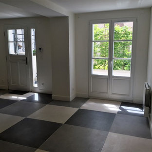 Entryway - large transitional ceramic floor and gray floor entryway idea in Paris with white walls and a white front door