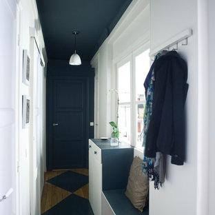 Réalisation d'une petit entrée design avec un sol en bois peint, un couloir et un mur blanc.