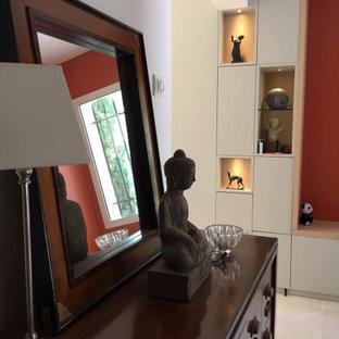 他の地域の大きい片開きドアトランジショナルスタイルのおしゃれな玄関ロビー (赤い壁、トラバーチンの床、濃色木目調のドア、ベージュの床) の写真