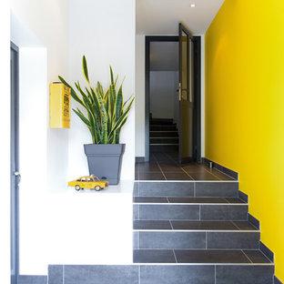 Diseño de distribuidor urbano, pequeño, con paredes amarillas, suelo de pizarra, puerta simple, puerta metalizada y suelo negro