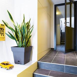 Modelo de distribuidor urbano, pequeño, con paredes amarillas, suelo de pizarra, puerta simple, puerta metalizada y suelo negro