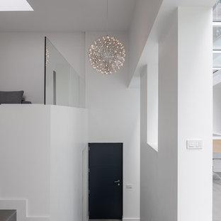 Bild på en funkis foajé, med vita väggar, granitgolv, en enkeldörr, en svart dörr och grått golv