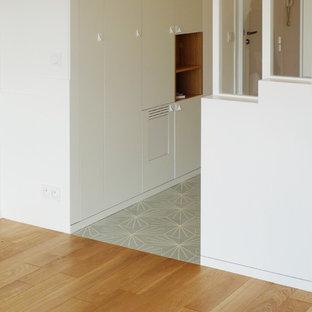Modern inredning av en liten hall, med vita väggar, en enkeldörr, en vit dörr, klinkergolv i keramik och turkost golv