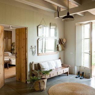 Свежая идея для дизайна: большая прихожая в стиле кантри с бежевыми стенами, бетонным полом и стеклянной входной дверью - отличное фото интерьера