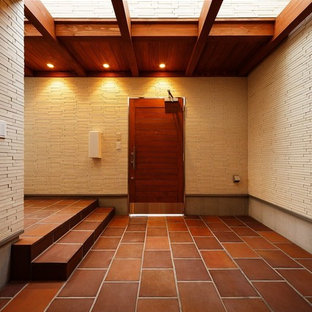 Example of a large minimalist terra-cotta tile, brown floor and wood ceiling entryway design in Osaka with a medium wood front door and white walls