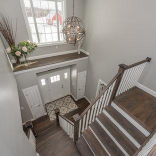 Bild på en mellanstor vintage entré, med grå väggar, mörkt trägolv, en enkeldörr, en vit dörr och brunt golv