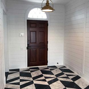 他の地域の広いダッチドアビーチスタイルのおしゃれな玄関ロビー (白い壁、塗装フローリング、木目調のドア、マルチカラーの床) の写真