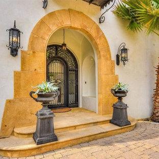 オースティンの中くらいの回転式ドア地中海スタイルのおしゃれな玄関ドア (白い壁、黒いドア、黄色い床) の写真