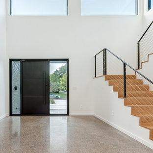 Cette photo montre une porte d'entrée moderne avec un mur gris, béton au sol, une porte pivot, une porte noire, un sol gris et un mur en parement de brique.