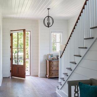 チャールストンの中くらいの片開きドアビーチスタイルのおしゃれな玄関 (白い壁、淡色無垢フローリング、木目調のドア、茶色い床) の写真