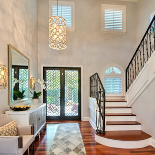 Entryway - transitional painted wood floor and brown floor entryway idea in Miami with gray walls and a glass front door