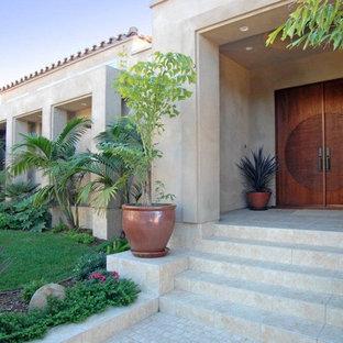 Entryway - large mediterranean limestone floor and brown floor entryway idea in San Diego with a dark wood front door and beige walls
