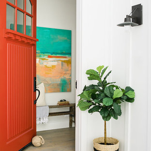 ロサンゼルスの片開きドアビーチスタイルのおしゃれな玄関ドア (白い壁、無垢フローリング、赤いドア、茶色い床) の写真