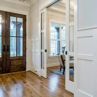 Mid-sized cottage medium tone wood floor and brown floor entryway photo in Raleigh with gray walls and a brown front door