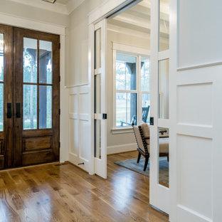 Bild på en mellanstor lantlig hall, med grå väggar, mellanmörkt trägolv, en dubbeldörr, en brun dörr och brunt golv