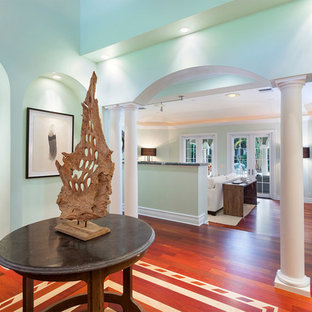 Mid-sized tuscan medium tone wood floor and red floor entryway photo in Miami with green walls and a medium wood front door