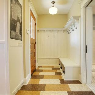 シアトルのトラディショナルスタイルのおしゃれなマッドルーム (黄色い壁、リノリウムの床、木目調のドア) の写真